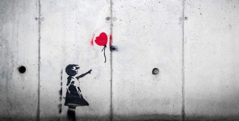 Stencil wall graffiti of a girl reaching for a red heart balloon, Photo by Karim MANJRA on Unsplash