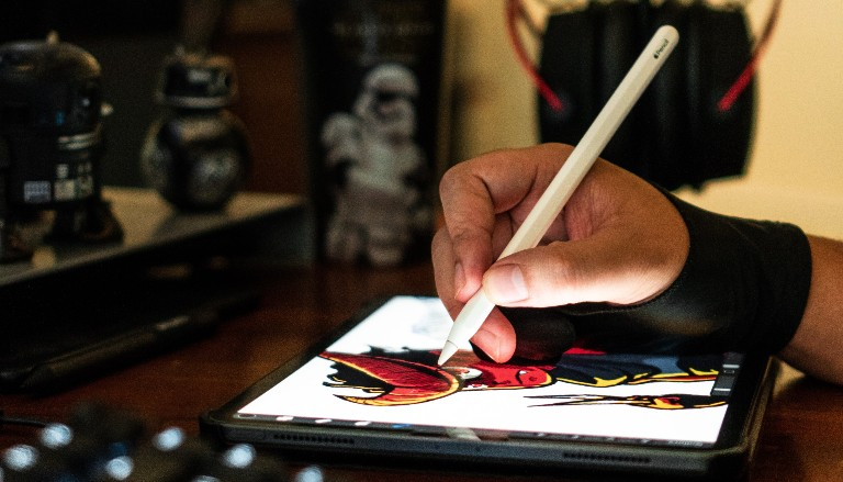 Drawing with a tablet and stylus. Photo by Clint Bustrillos on Unsplash