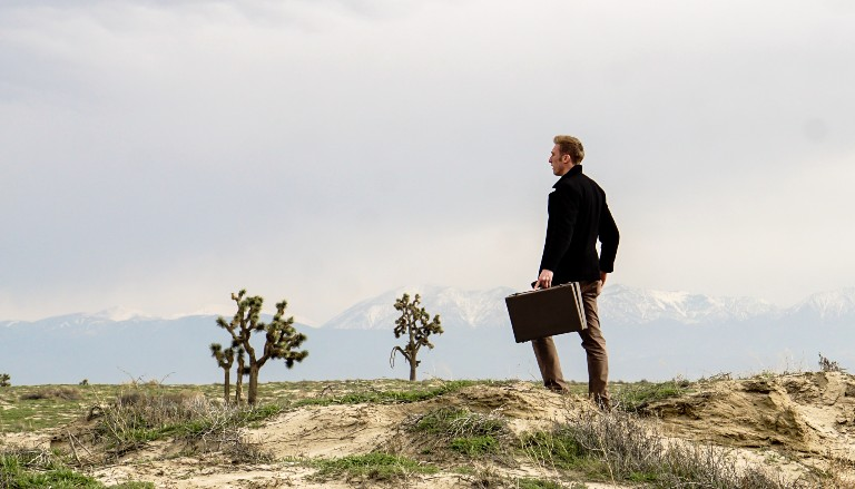 Man on hillside with briefcase. Photo by Fred Kearney on Unsplash