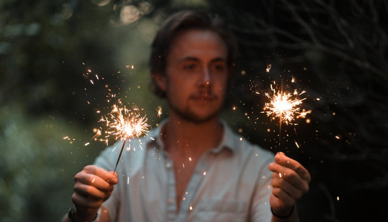 Man holding two lit sparklers. Photo by Ethan Hoover on Unsplash