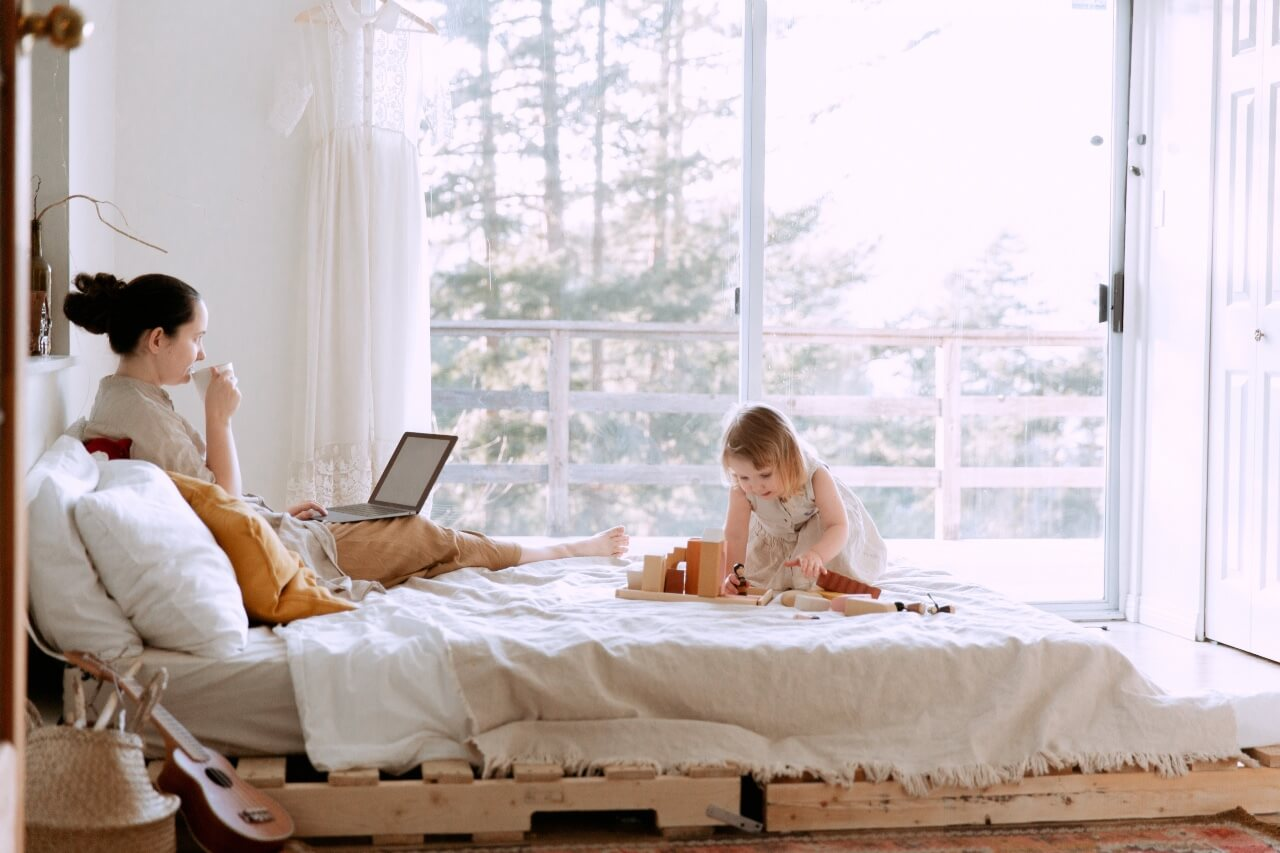 Woman works on laptop in bed while her young child plays