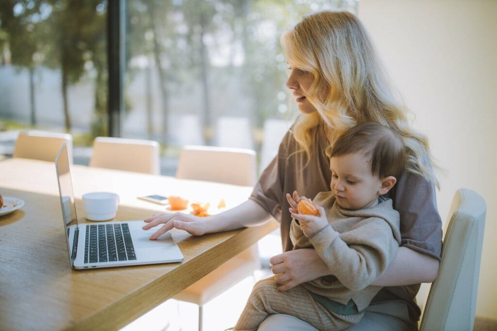 A lady works at her laptop with a young child on her lap