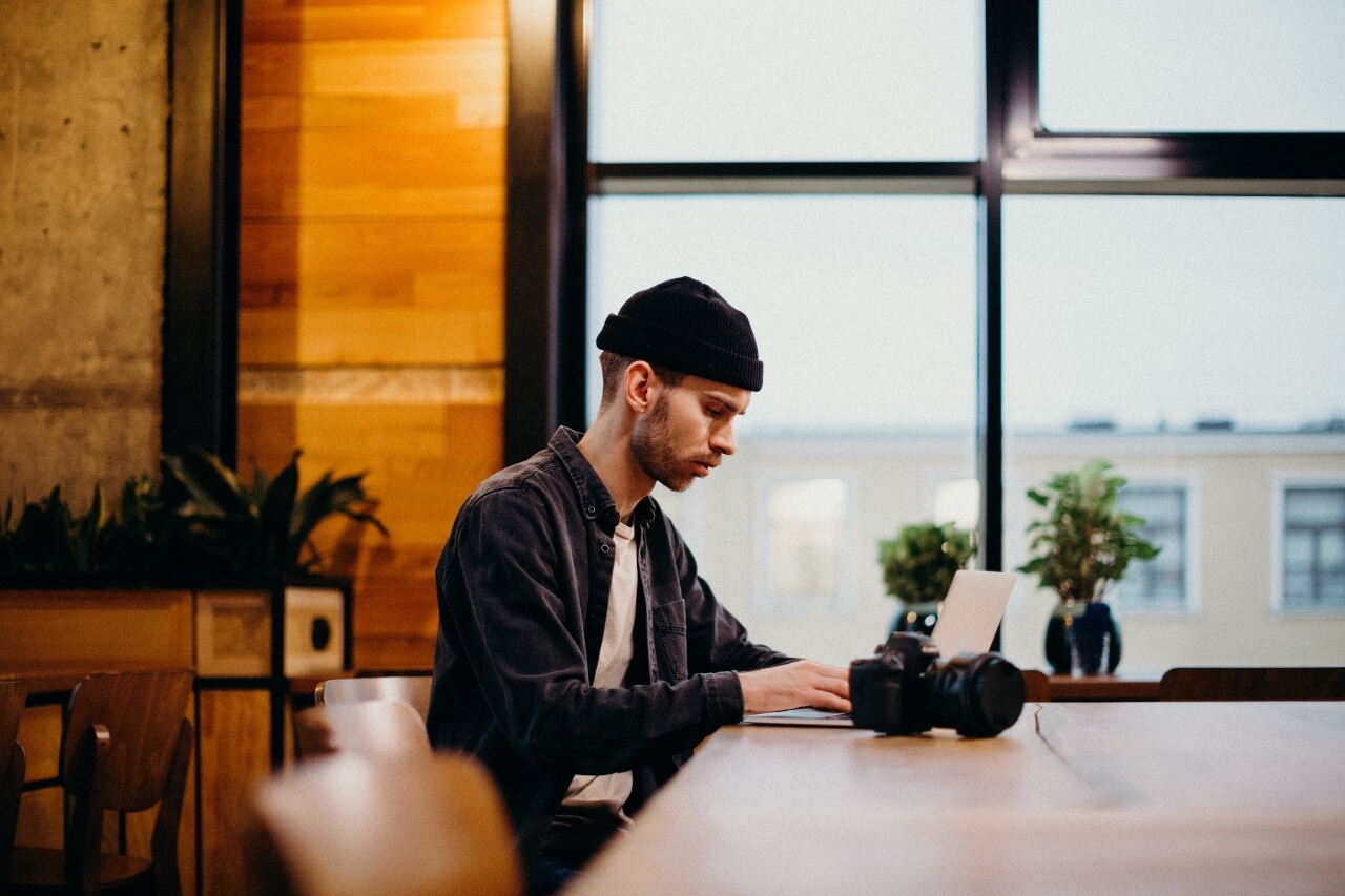 a man sits at a table working on a laptop with a camera beside him