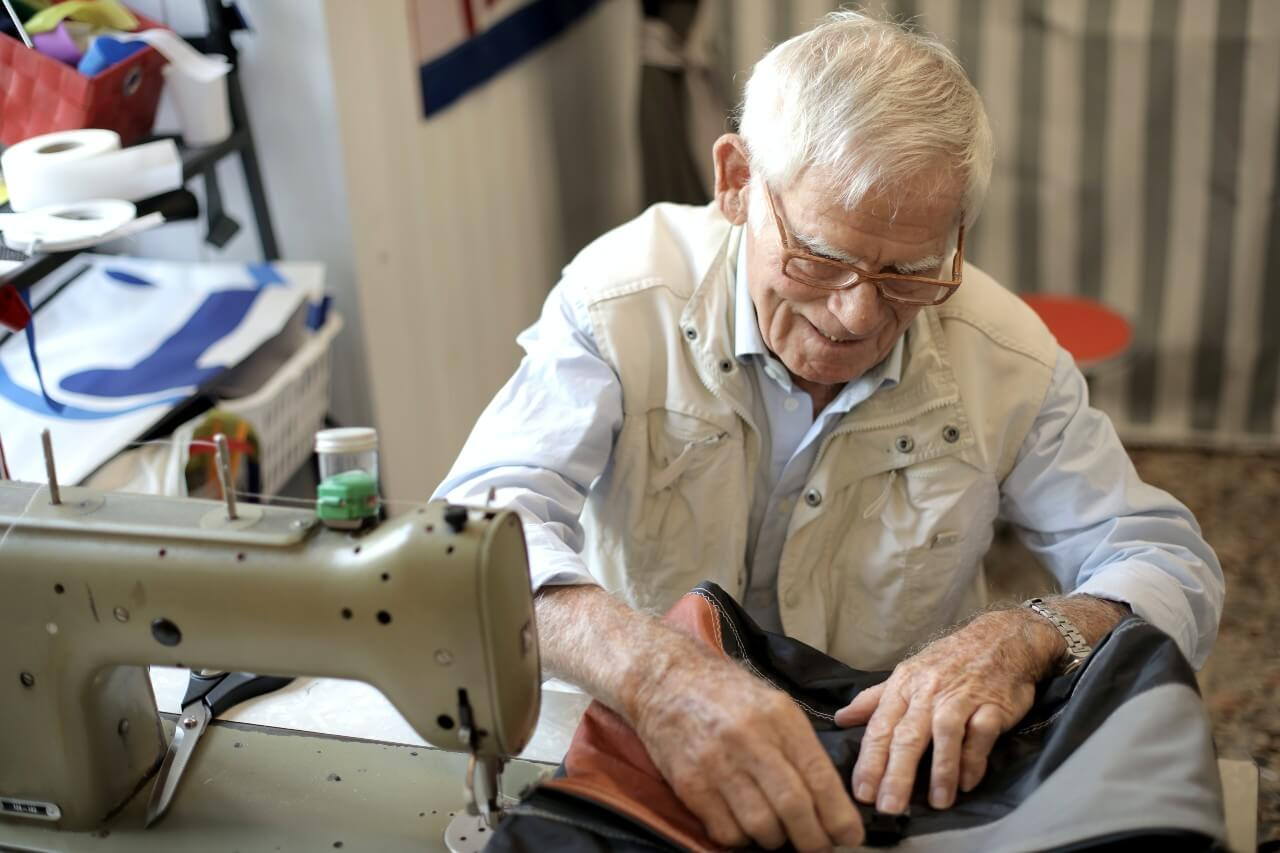 An elderly gentleman uses a sewing machine