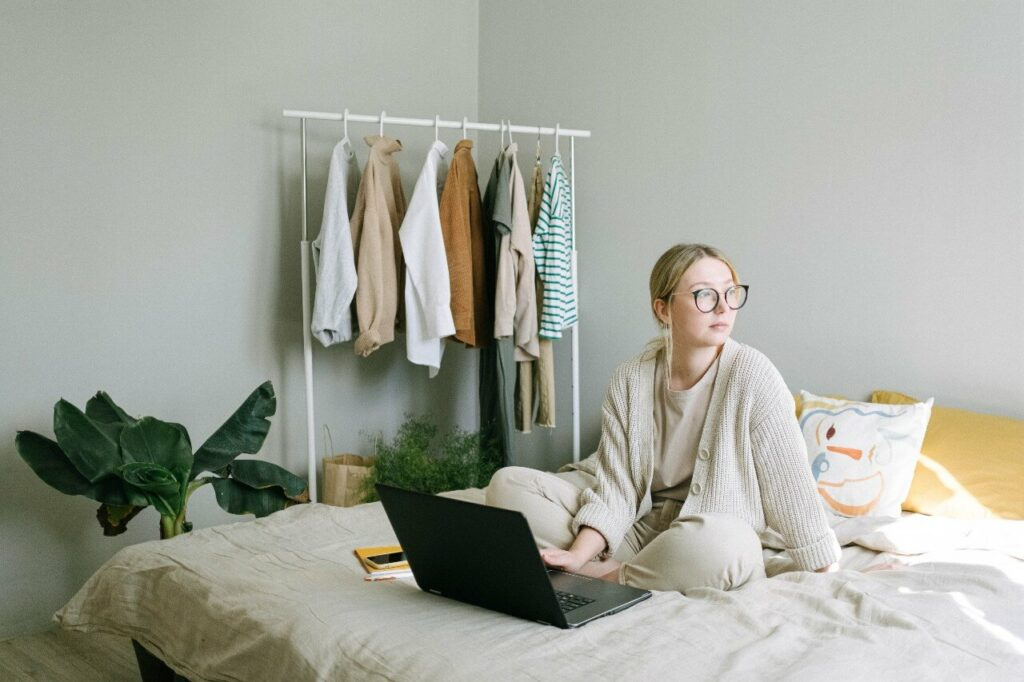 Woman in cream cardigan sits on bed working on laptop