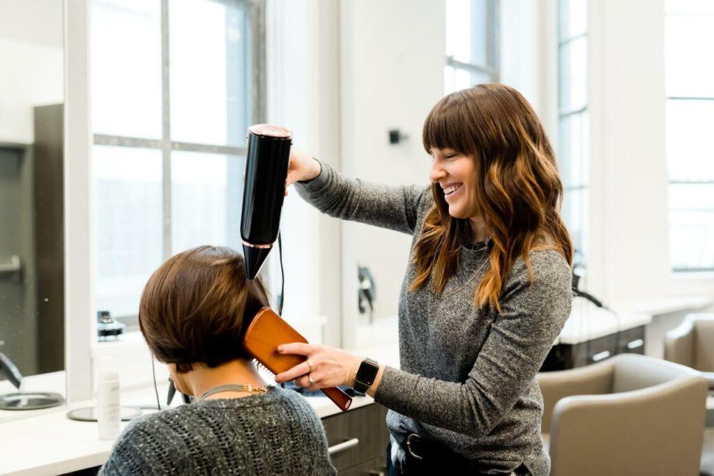 A hairdresser blowdries her client's hair