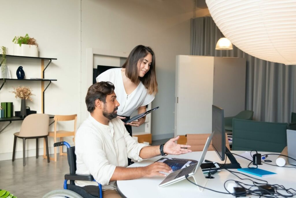 A man in a wheelchair works with his female colleague at a computer screen