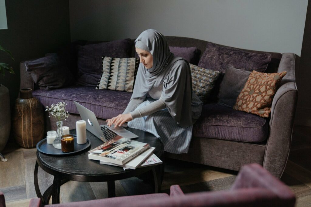 Lady in a grey hijab works at laptop