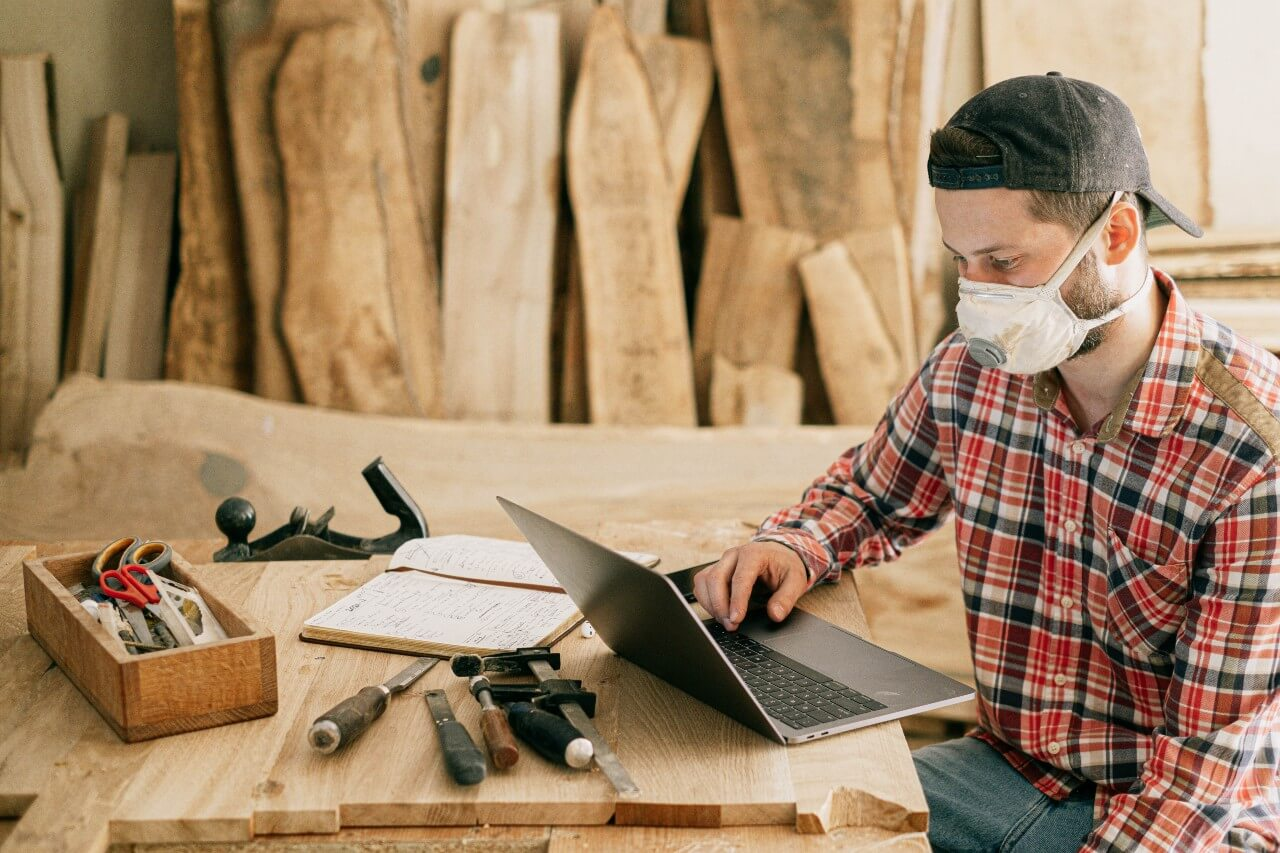 Man using a laptop in a woodworking workshop