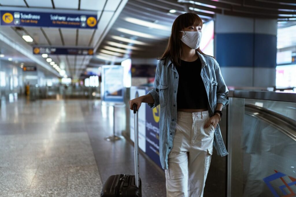 A lady waits for her flight in an airport, wearing a face covering and holding her suitcase