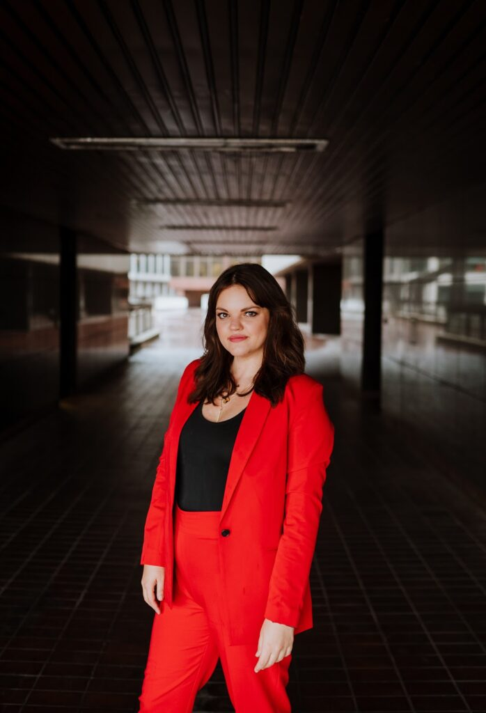 Kirsty Hulse is posing for a photo, and wearing a powerful red suit