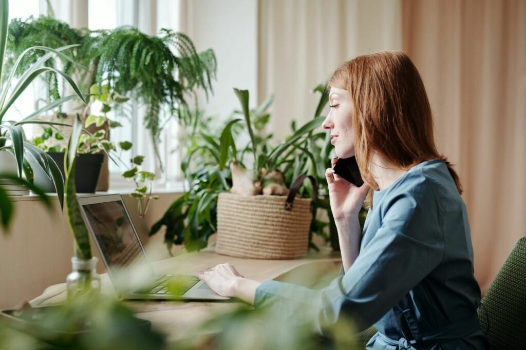 A woman sits at a desk surrounded by plants, talking on the phone