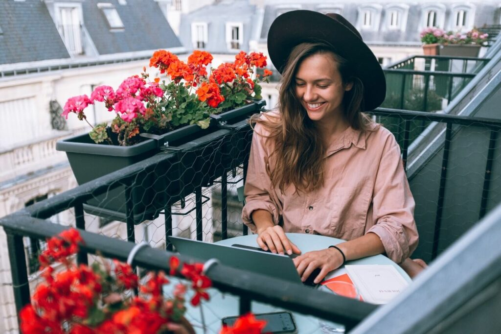 A lady in a pink shirt wearing a hat works at her laptop outside on a balcony