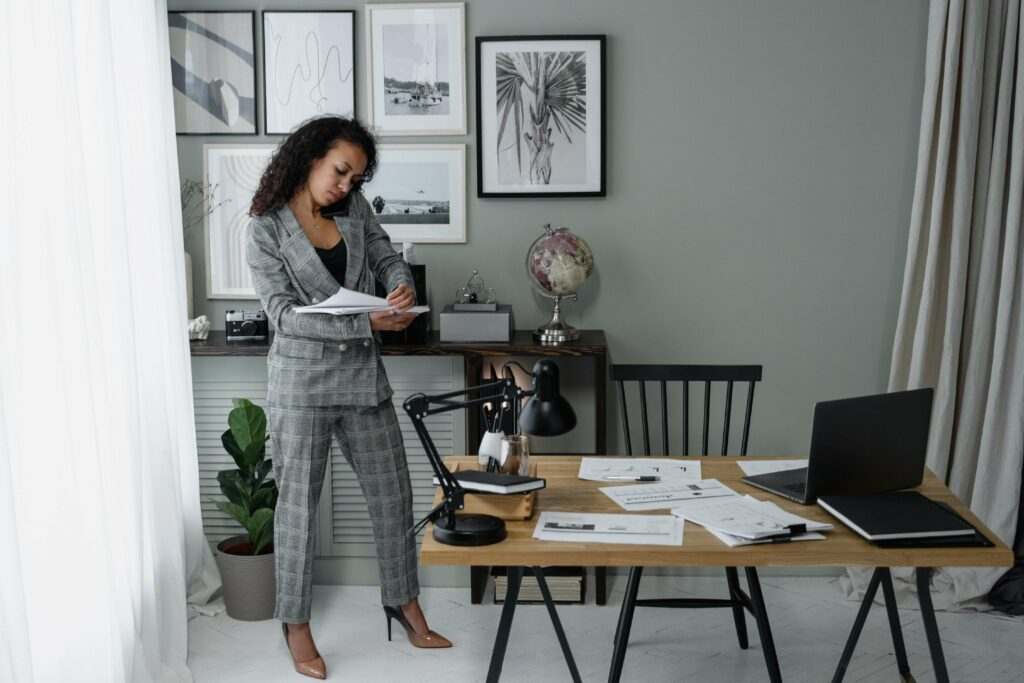 A lady in a grey suit stands looking at paperwork while on the phone