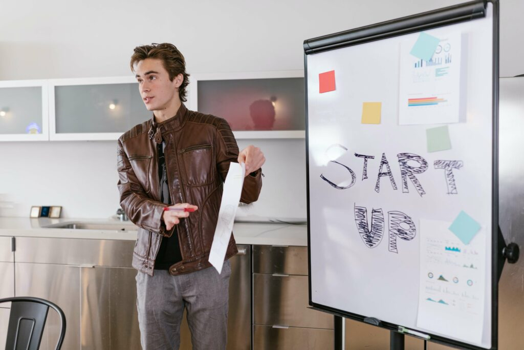 """A man in a brown leather jacket gives a presentation standing next to a whiteboard which says """"start up"""""""