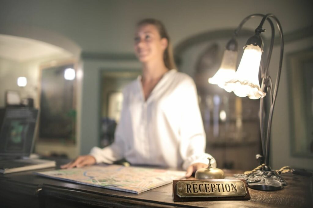 A lady wearing a white shirt stands behind a reception desk with a map in front of her