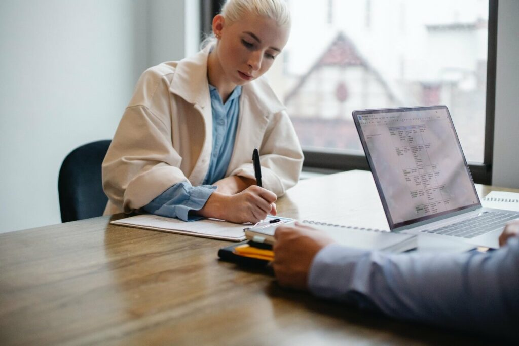 Woman with blonde hair makes notes during a meeting