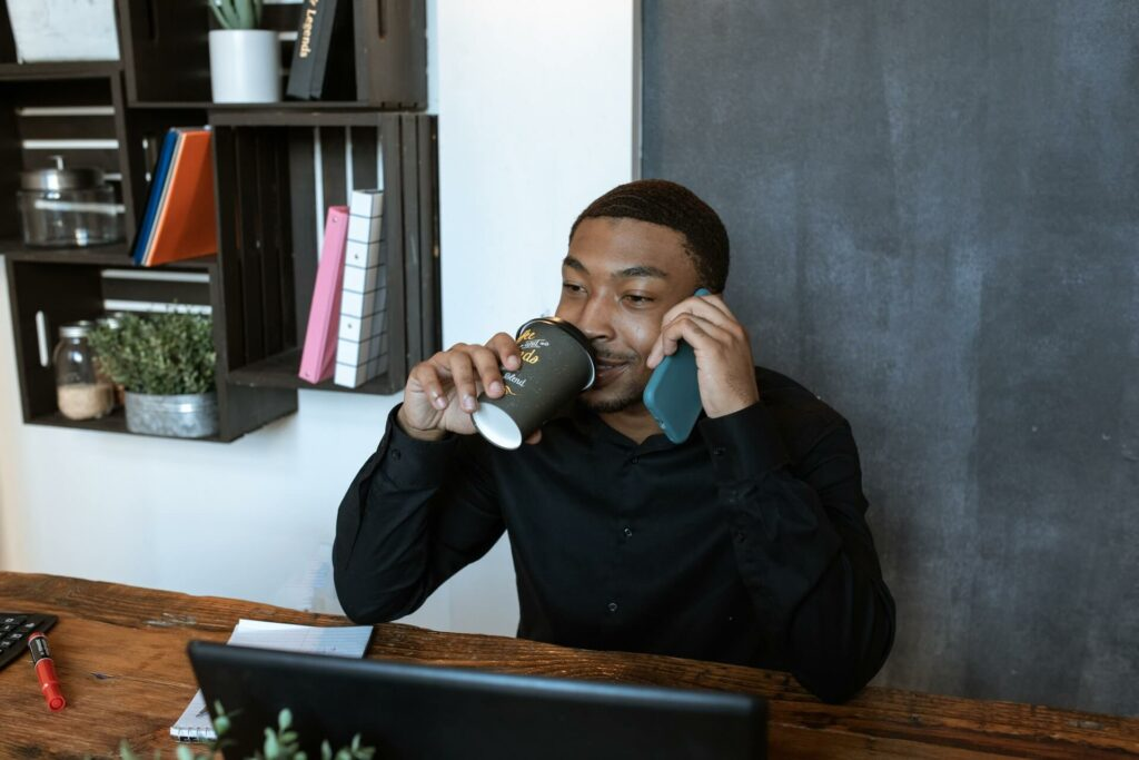 A man looks at his laptop screen while drinking a coffee and speaking on the phone