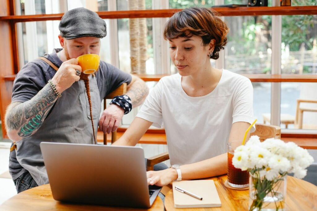 A woman in a white top shows a man wearing a cap and drinking a cup of tea something on her laptop screen