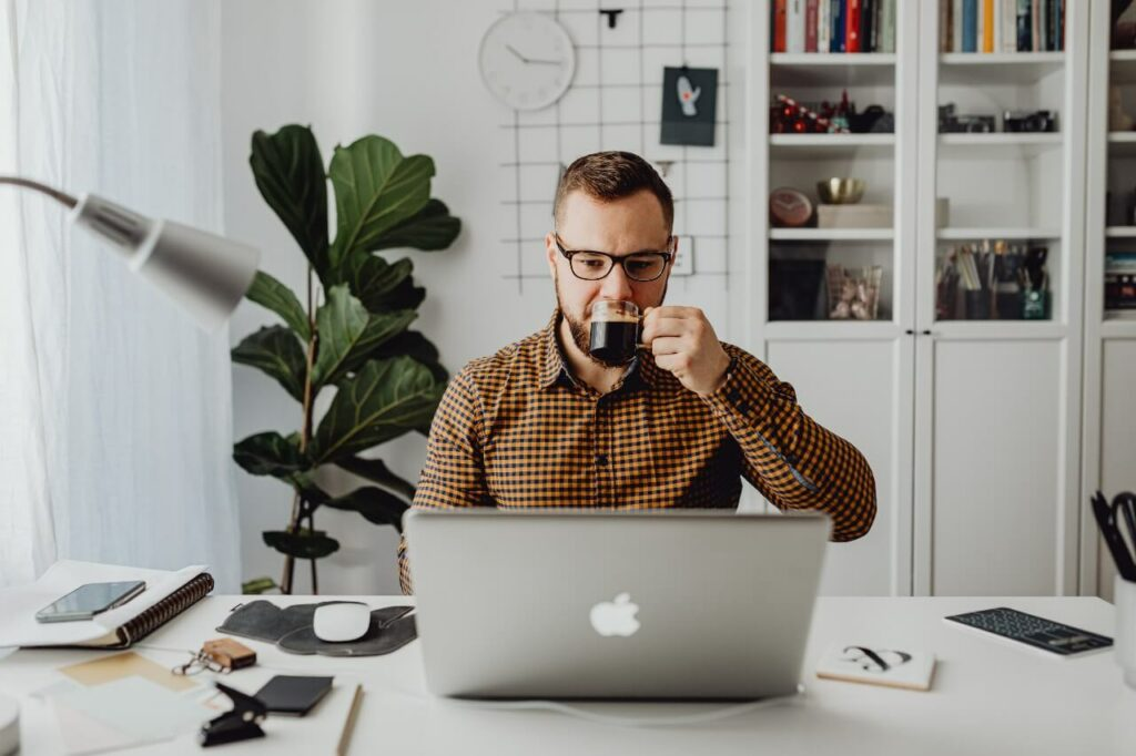 A man in a brown shirt drinks coffee while working on a Macbook