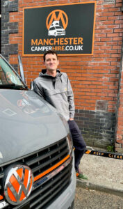 Nick, owner of Manchester Camper Hire stands in front of sign that reads manchestercamperhire.co.uk