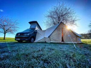 VW camper van parked in a field with a bell tent extension erected to the side