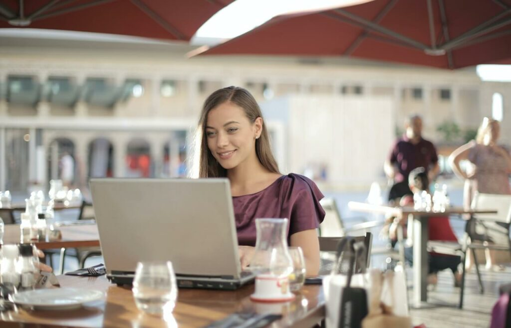 Lady wearing purple top sits in cafe working at a laptop