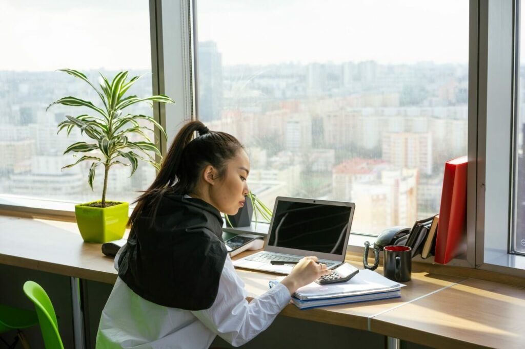 A woman sits at a window desk working at a laptop, working out calculations with a calculator